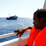 A migrant on the MOAS ship MV Phoenix looks at the wooden boat from which he was rescued 10.5 miles (16 kilometres) off the coast of Libya